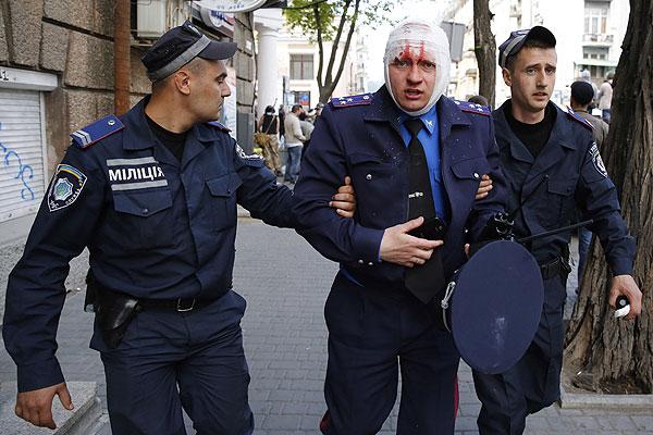 Сотрудники одесской милиции ведут под руки раненого коллегу.