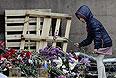 Мужчина с девочкой возлагают цветы в память о погибших в результате пожара в Доме профсоюзов на площади Куликово Поле в Одессе.