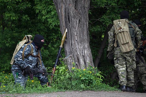 Люди в камуфляже с оружием на позициях.