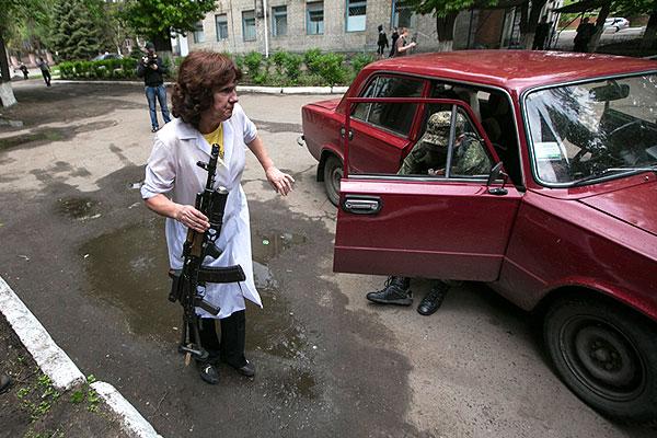 Медицинский работник помогает раненному в боях на окраине Славянска бойцу ополчения выйти из автомобиля, на котором его привезли в больницу местные жители.