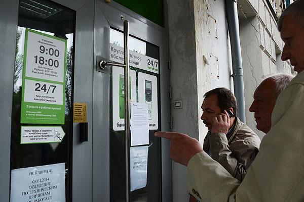 Жители Донецка у офиса Приватбанка на улице Горова в Донецке. Приватбанк временно приостановил работу своих офисов и банкоматов в Донецкой и Луганской областях.
