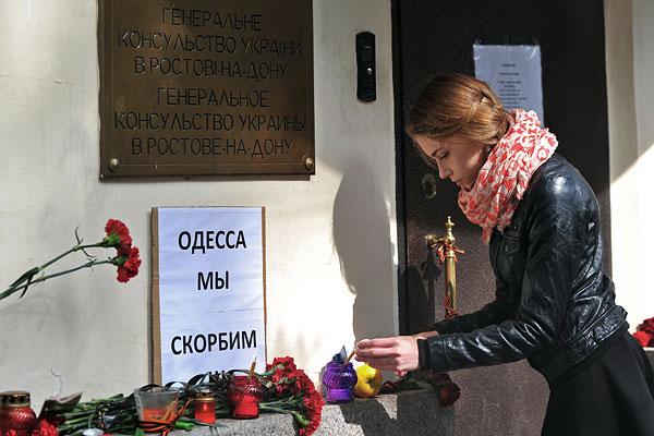 Девушка зажигает свечу у генерального консульства Украины в Ростове-на-Дону.