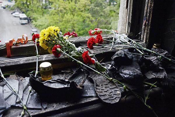 Цветы на разбитом окне в память о погибших в результате пожара в Доме профсоюзов в Одессе.