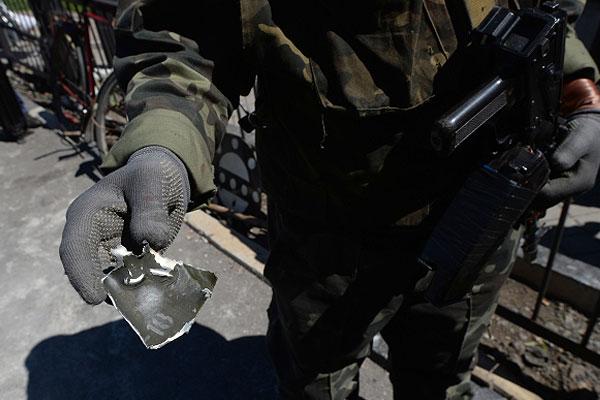 Боец самообороны демонстрирует осколок минометного снаряда на блокпосту у железнодорожного переезда в районе села Андреевка.