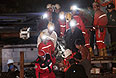 Группа турецких спасателей выносит на носилках пострадавшего от взрыва шахтера.