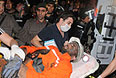 Пострадавшего шахтера подвозят к машине скорой помощи.