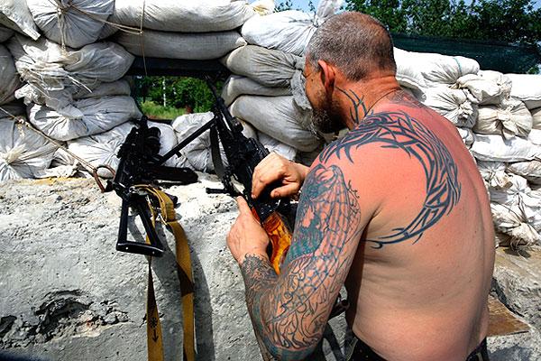 Ополченец с двумя автоматами в укреплении под Славянском.