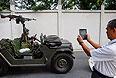 Мужчина снимает на планшет военный автомобиль в центре Бангкока.
