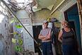Жители Славянска в своем разрушенном в результате ночного артобстрела доме.