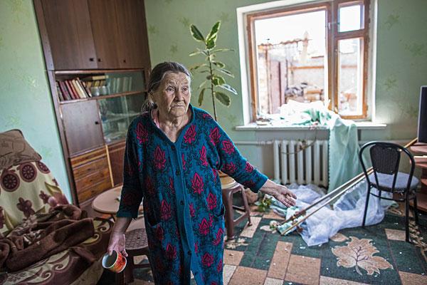 Пожилая женщина в своем доме, пострадавшем в результате ночного артобстрела.