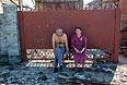Жители Славянска сидят у ворот своего дома, пострадавшего в результате ночного артобстрела.