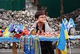Продавец сувениров у баррикад, оставшихся на одной из улице Киева.
