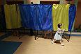 Девочка несет бюллетени на одном из избирательных участков.