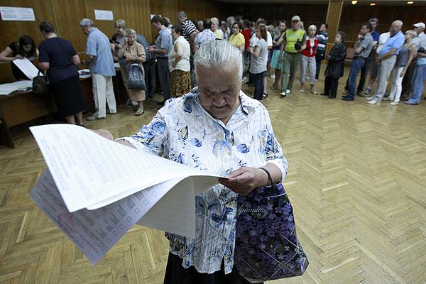 Женщина рассматривает бюллетень в Киеве.