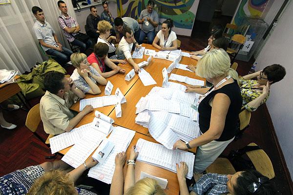 Избирательная комиссия во время подсчета голосов на одном из избирательных участков в Киеве.