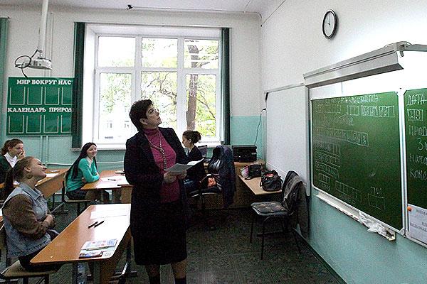 Преподаватель смотрит на часы перед началом сдачи единого государственного экзамена по русскому языку в средней образовательной школе №28 города Владивостока.