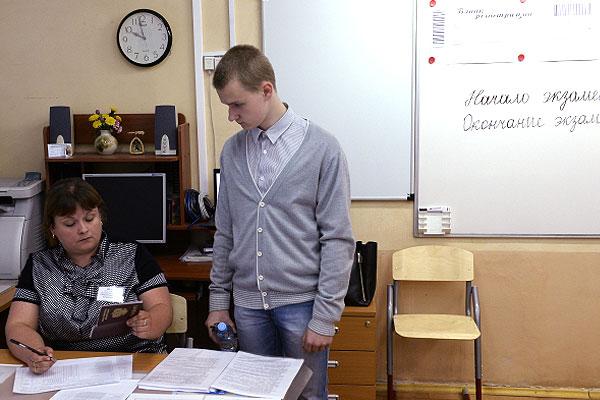 Учитель проверяет паспорт ученика перед сдачей единого государственного экзамена по русскому языку в школе № 1400 Москвы.