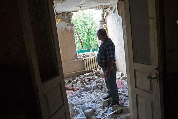 Мужчина в комнате своего дома, разрушенного в результате попадания снаряда во время обстрела украинскими силовиками, в поселке Червоный Молочар возле Славянска.