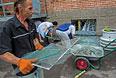 Работники больницы убирают осколки разбитых стекол, которые были выбиты при попадании снаряда в здание больницы в Славянске во время обстрела украинскими силовиками жилых районов города.