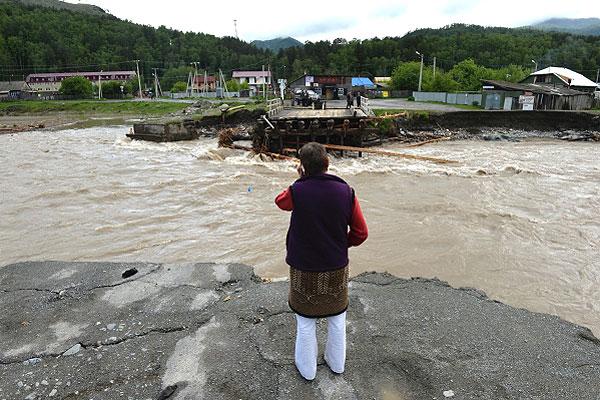 Местная жительница говорит по мобильному телефону у разрушенного паводком моста на реке Чемалка в селе Чемал. Из-за проливных дождей произошел подъем уровня воды в реках, что привело к подтоплениям на территории Республик Хакасия и Алтайского края.