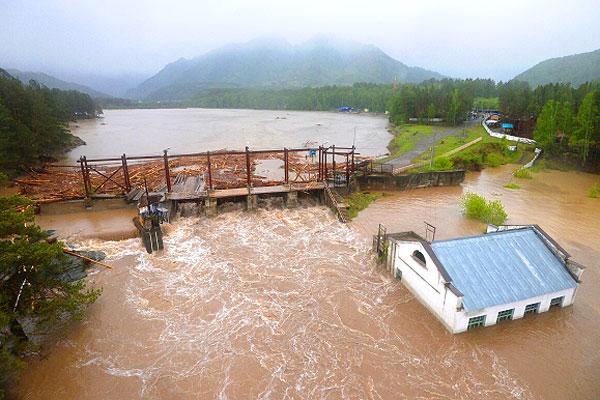 Затопленное здание чемальской ГЭС и плотина ГЭС на реке Чемалка во время паводка.