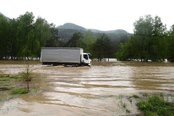 Грузовик в селе Майма, затопленном вышедшей из берегов рекой Катунью.