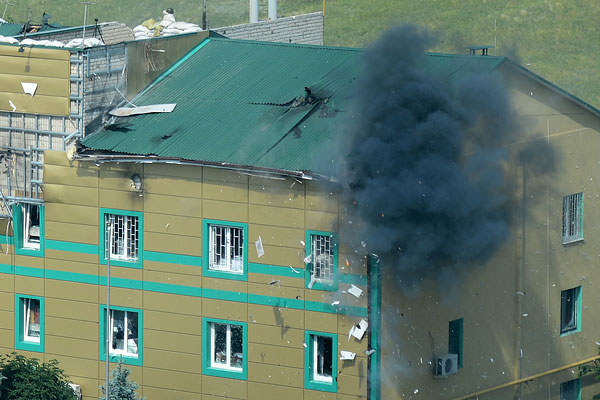 Попадание снаряда из гранатомета в здание воинской части погранслужбы Украины на окраине Луганска во время боев ополченцев с украинскими погранвойсками.