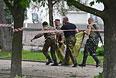 Народные ополченцы несут тело погибшего в результате авиаатаки на здание обладминистрации в Луганске.