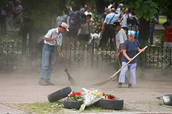 Жители убирают территорию вокруг здания областной администрации Луганска после авиаатаки 2 июня.