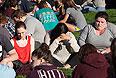 Студенты молятся на лужайке кампуса.