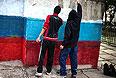 Луганские подростки разукрашивают опору в цвета российского флага.