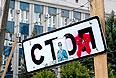 """Забор из колючей проволоки, знак """"Стоп"""" и икона на площади перед зданием СБУ в Луганске."""