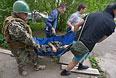 Ополченцы эвакуируют раненого во время боя.