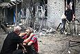Мужчина утешает соседа возле разрушенного дома в поселке Станица Луганская.