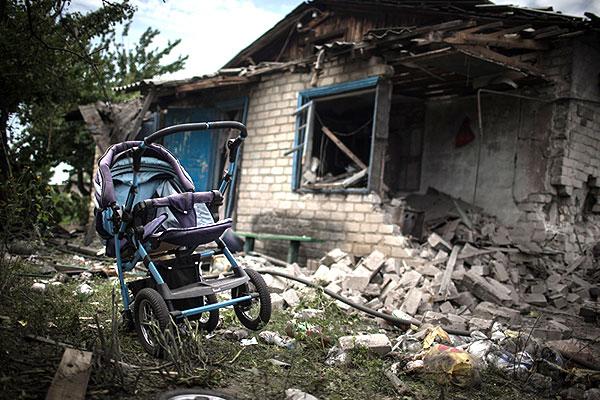 Детская коляска во дворе разрушенного дома.
