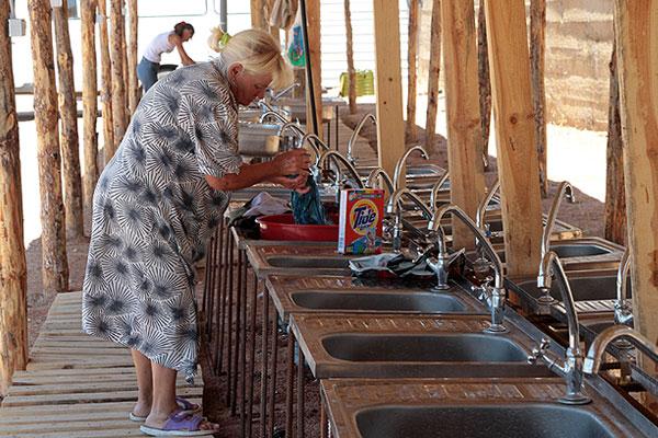 Женщины занимаются стиркой в оборудованной санитарной зоне.