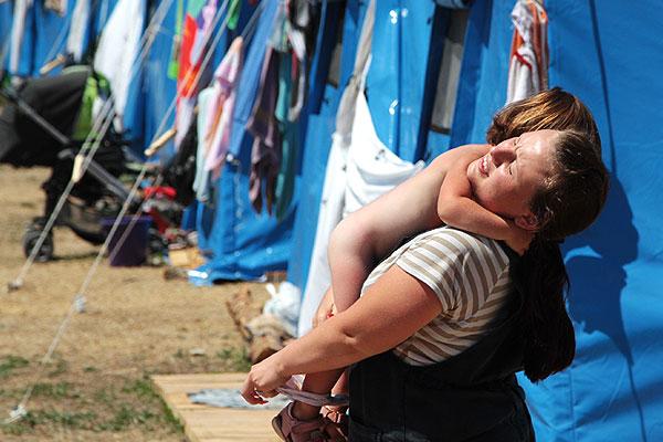 Женщина переодевает ребенка на территории севастопольского лагеря для беженцев.
