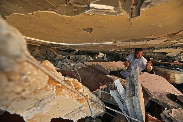 Палестинец ищет вещи под обломками дома.