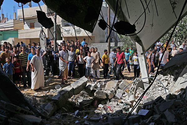 Палестинцы собираются вокруг дома, который был разрушен в результате бомбардировок израильских ВВС на юге сектора Газа.