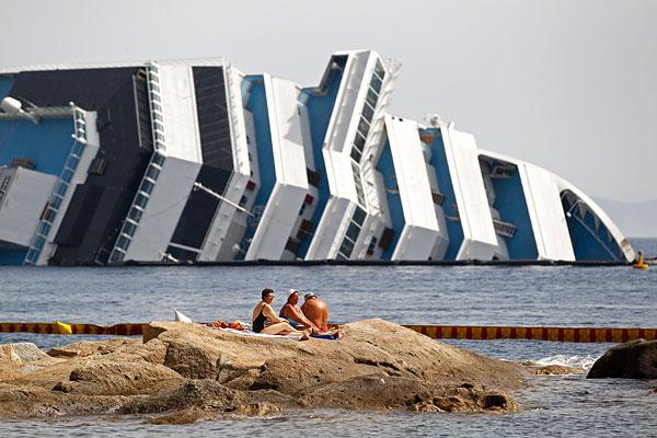 Отдыхающие загорают рядом с затонувшим лайнером.