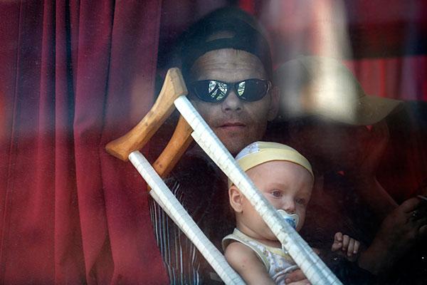 Мужчина с ребенком на руках смотрит из окна автобуса, уезжающего в Россию.