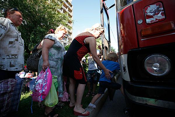Жители Донецка садятся в автобус.