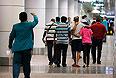 Люди, ожидавшие рейс MH17, покидают международный аэропорт Куала-Лумпур.