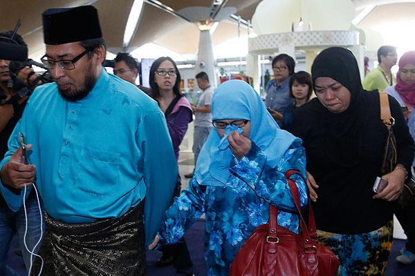 Люди прибывают в зону ожидания аэропорта Куала-Лумпур.