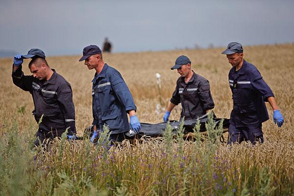 Сотрудники ГСЧС несут тело погибшего.