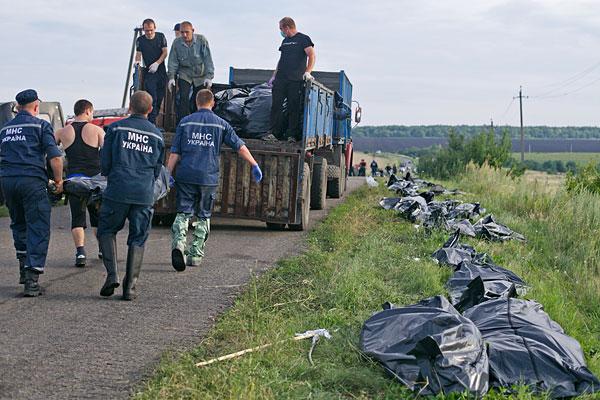 Сотрудники ГСЧС собирают тела погибших на месте падения самолета.