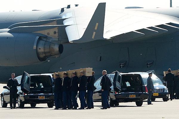 Перенос тел погибших из самолета в катафалки для транспортировки на военную базу в городе Хилверсум на севере Нидерландов.