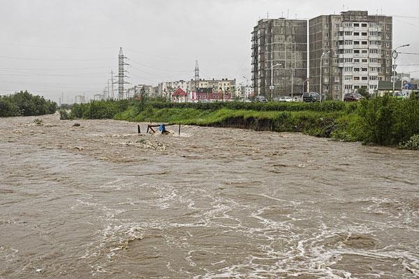 Река, разлившаяся после прошедших ливней, в одном из районов города.