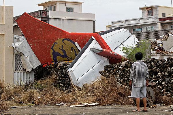 Тайванец во дворе своего дома смотрит на обломки самолета.