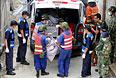 Спасатели собирают тела погибших.